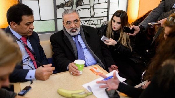 Syrian Information Minister Omran al-Zohbi (second from left) speaks to journalists during a break in talks