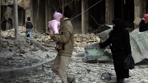 Syrians walk along a destroyed street following a reported airstrike by government forces on the northern Syrian city of Aleppo