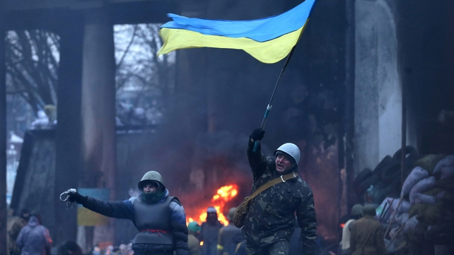 A protester waves a Ukrainian national flag near one of the barricades in Kiev (Pic: EPA)