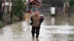A man holds a girl on his back in a flooded street of the French village of Larreule