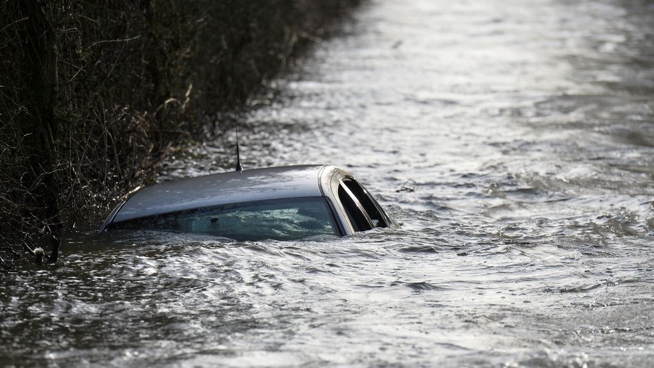 A car is seen submerged on the side of a flooded road leading into Muchelney