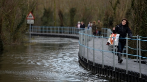 A woman walks along a floating pontoon walkway installed over flood water in the cut-off village of Muchelney in Somerset