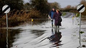 A couple approach flood water on the road at Burrow Bridge in Somerset, England