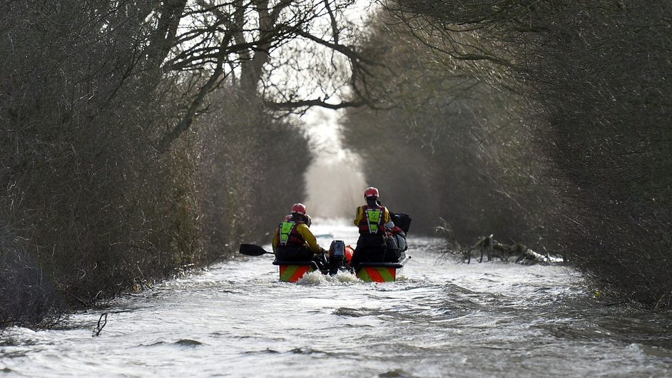 A boat operated by emergency services transports residents through flood water to the cut-off village of Muchelney in Somerset, southwest England