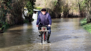A man rides his bicycle in a a flooded street of the French southwestern village of Caixon after heavy rain hit the region