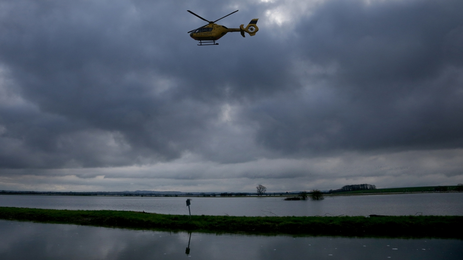 A helicopter flies over flood water at Muchelney