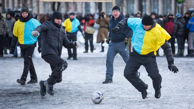 Anti-government protesters play football in the city centre