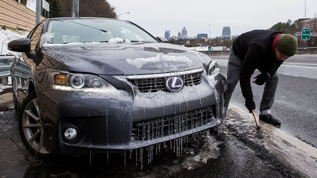 A man works to clear ice and retrieve the car he abandoned on an exit ramp in Atlanta