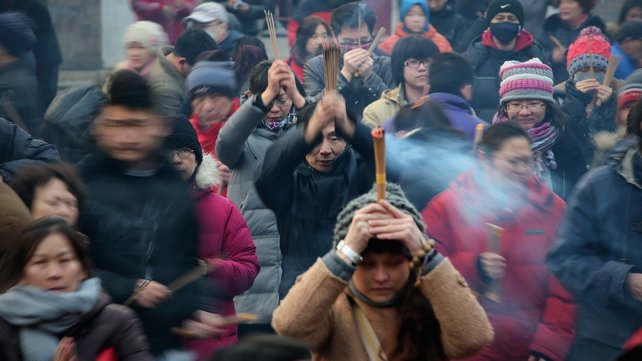 Chinese people pray for good fortune as they hold burning incense