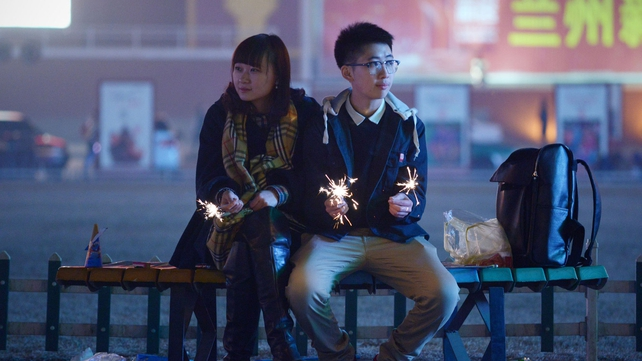 A couple hold fireworks as they sit together on a bench in Lanzhou, in Gansu province