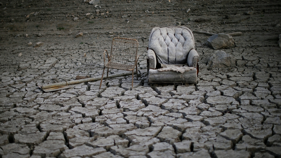 Chairs sit in dried and cracked earth that used to be the bottom of the Almaden Reservoir in San Jose, California