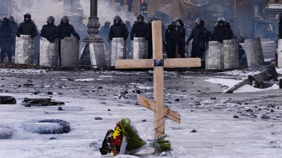 A cross is placed in front of riot policemen at a road block in Kiev, Ukraine