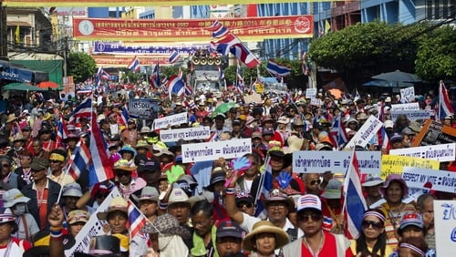Anti-government protesters wave national flags as they parade during a rally at Chinatown in Bangkok