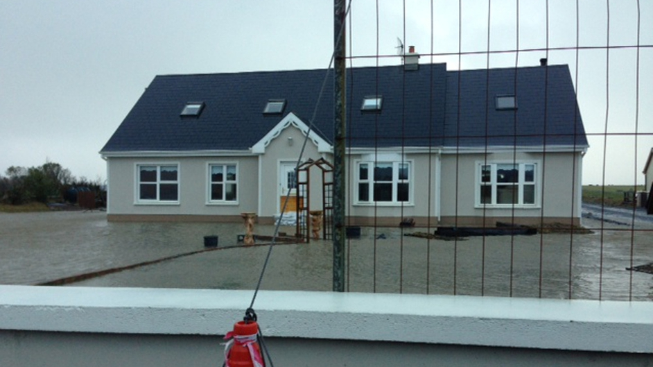 A house in Quilty, Co Clare stands isolated by flood waters