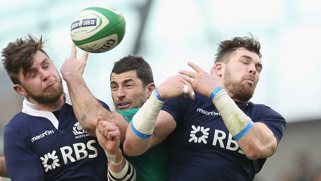 Rob Kearney of Ireland attempts to catch the ball as Ryan Wilson (L) and Sean Lamont challenge