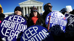 Pro-choice activists hold signs as marchers of the annual March for Life arrive in front of the US