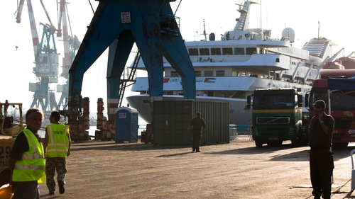 Israeli soldiers and port workers stand next to the Mavi Marmara, at Ashdod Port