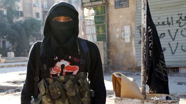 A member of jihadist group al-Nusra Front stands in a street of the northern Syrian city of Aleppo
