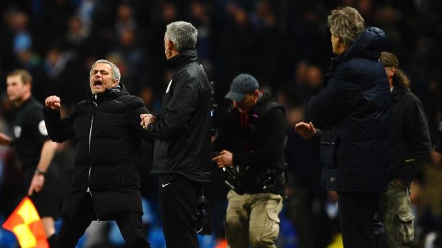 Jose Mourinho (L) celebrates victory as Manuel Pellegrini looks on