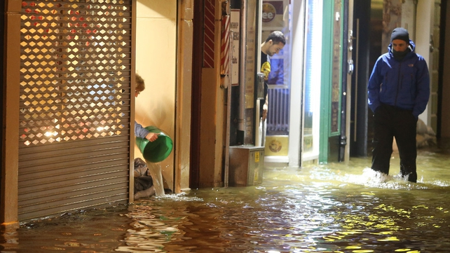 A woman bails out water from a shop as flood water rises in Cork city