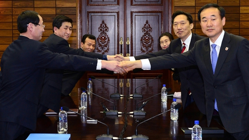 Delegations from North and South Korea shake hands over the reunion agreement