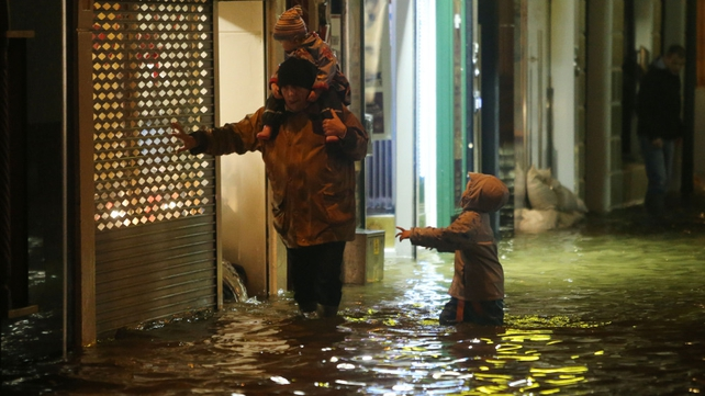 A man and two children make their way through a flooded street in Cork