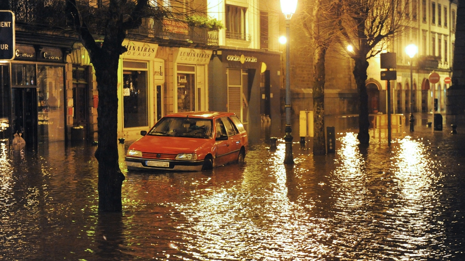A car in a flooded street in the centre of Morlaix, western France