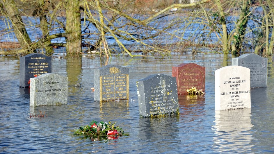 Headstones half-submerged in flood water in a graveyard in the village of Moorland, Somerset Levels, south west England (Pic: EPA)