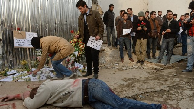 Afghan independent civil society activists pay tribute to the victims of an attack, as an activist mimics death in front of the restaurant in Kabul