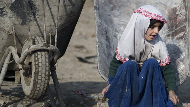 Afghan girl, Habiba sits near a wheelbarrow as she waits for food donations from the World Food Programme (WFP) in Kabul