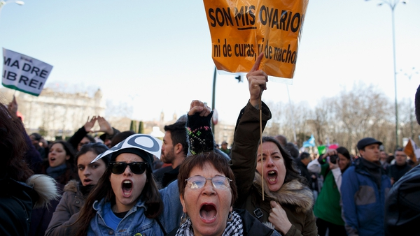 Protesters shout slogans and hold a placard reading 'they are my ovaries, nor of priest, nor of males' during a pro-choice protest in Madrid