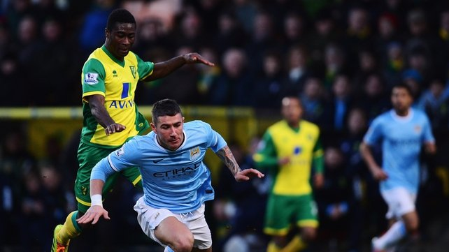 Alexander Tettey of Norwich tackles Aleksandar Kolarov of Manchester City
