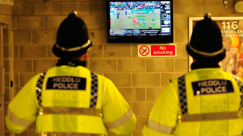 Policemen watch the 6 Nations match between Ireland and Wales before the Premier League match between Swansea and Cardiff at Liberty Stadium