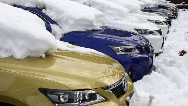 Lexus vehicles are covered with snow at a vehicle shop in Tokyo