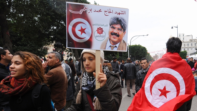 A Tunisian woman holding a placard of portrait of assassinated Tunisian opposition figure Mohamed Brahmi walks past a man wearing the country's national flag