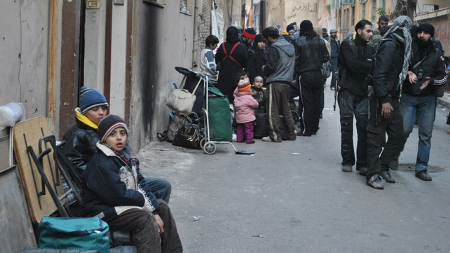 Syrians gather with their belongings in a street of a besieged district of the central city of Homs