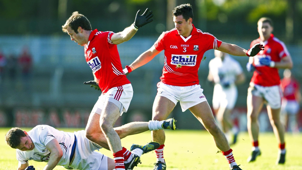 Kildare's Eoghan O'Flaherty is tackled by James Loughrey and Tom Clancy of Cork