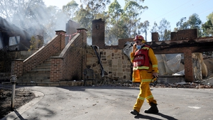 A member of the Country Fire Authority walks past a destroyed house in the Warrandyte suburb of Melbourne