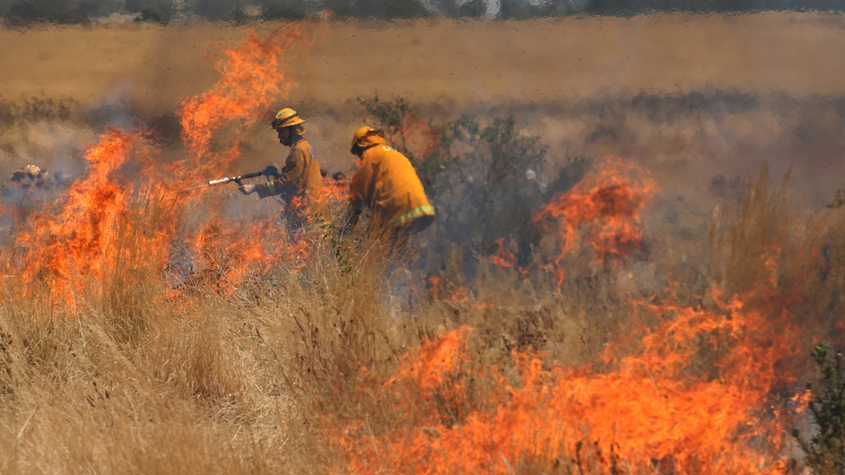 Firefighters battle a fast moving grass fire close to homes in the Melbourne suburb of Craigieburn