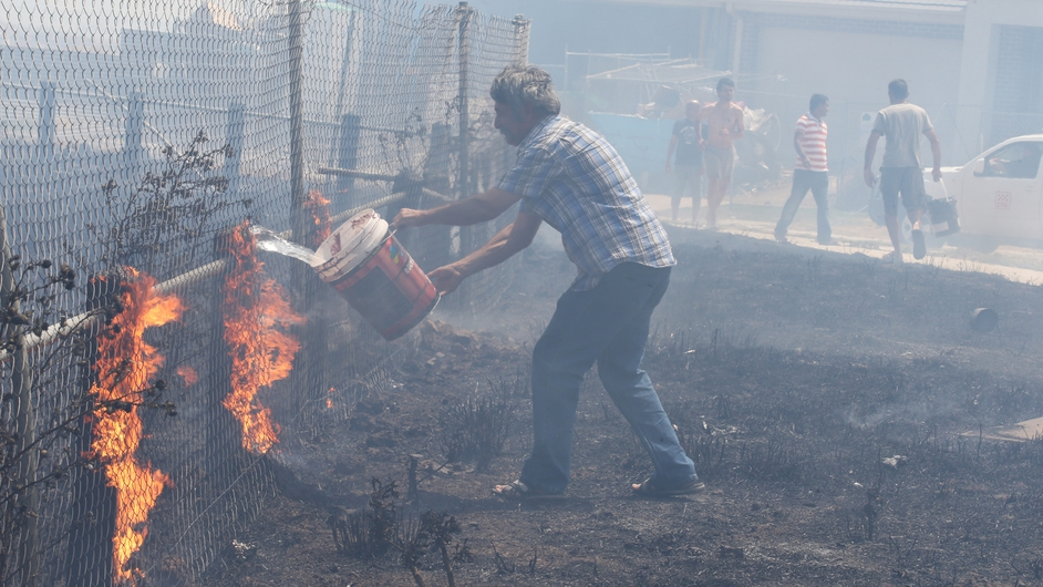 A man tackles a fire in his garden in Craigieburn
