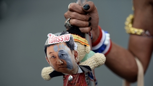 An protester holds a doll with a picture of former PM Thaksin Shinawatra and the word 'tyrant'