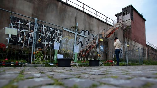 A woman stands next to a memorial for the victims in Duisberg