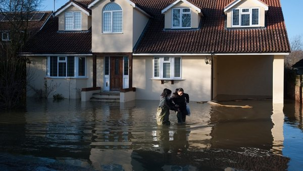 People wade through deep floodwater outside a home in Wraysbury, west of London