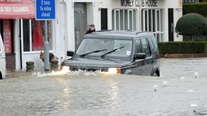 A car drives through flood waters in the village of Datchet in Berkshire (Pic: EPA)