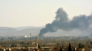 Smoke billows from buildings following a reported air strike by government forces on the Qadam suburb on the outskirts of the Syrian capital Damascus