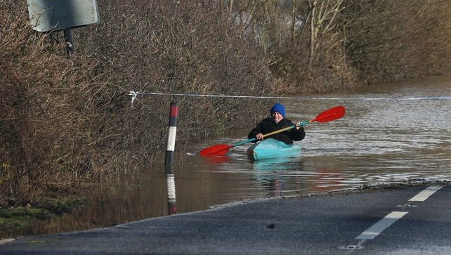 A man paddles his canoe down the flooded main A361 road as it enters the village of East Lyng