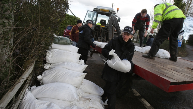 Police officers help unload sandbags from a tractor trailer in the village of East Lyng