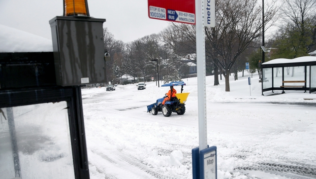 Transit Authority employees work to clear snow from bus stops in Washington DC