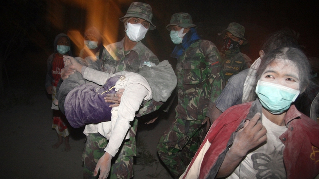 Indonesian soldiers evacuate ash covered residents in Malang, East Java province