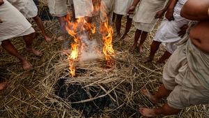 Devotees warm up by a fire before taking their holy bath (Pic: EPA)